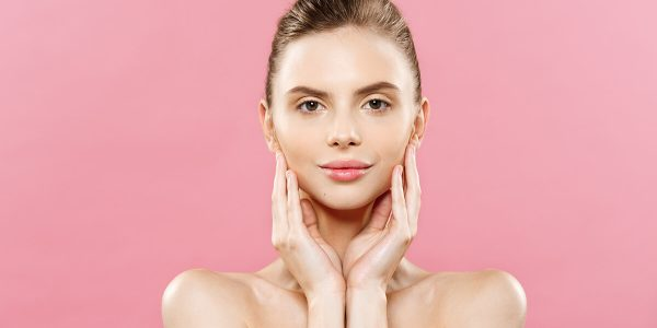 Beauty Spa Concept - Caucasian Woman with perfect face skin Portrait. Beautiful Brunette Spa Girl showing empty copy space. Isolated on pink studio background. Proposing a product. Gesture for advertisement.